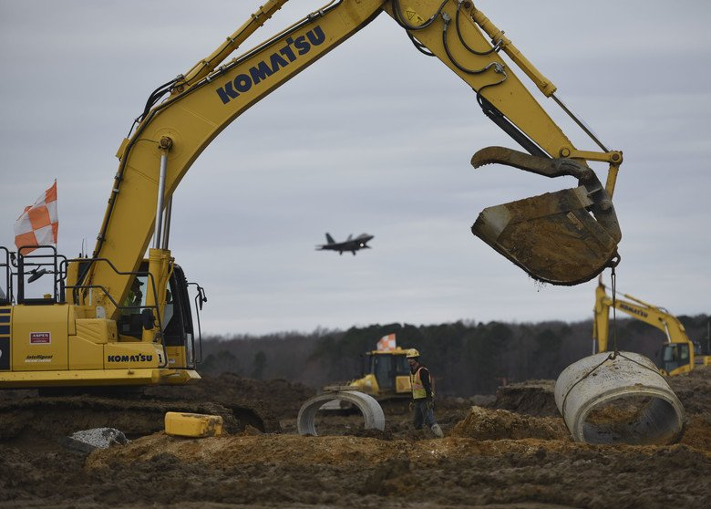 Aspen Construction workers move a segment of cement pipe on the airfield construction site at Joint Base Langley-Eustis, Virginia,