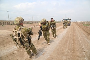 Australian soldiers with Task Group Taji pull a Bushmaster Protected Mobility Vehicle
