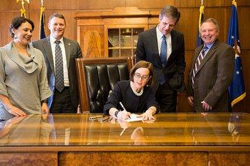 Gov. Kate Brown (center) signs Senate Bill 611 into law