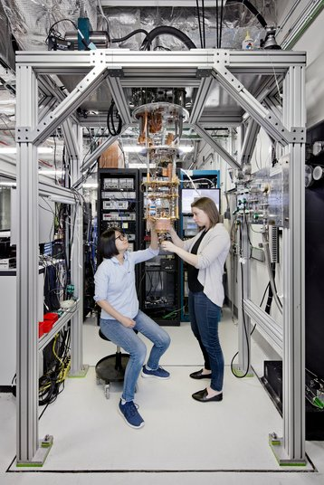 IBM Quantum Computing Scientists Hanhee Paik (left) and Sarah Sheldon (right) examine the hardware inside an open dilution fridge at the IBM Q Lab at IBM's T. J. Watson Research Center in Yorktown, NY.