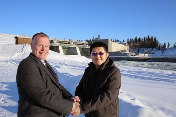 Erik Svensson and Canaan CEO N.G. Zhang in front of a hydro power plant on the Lulea river