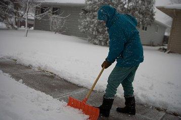 A North Dakota resident shovelling snow